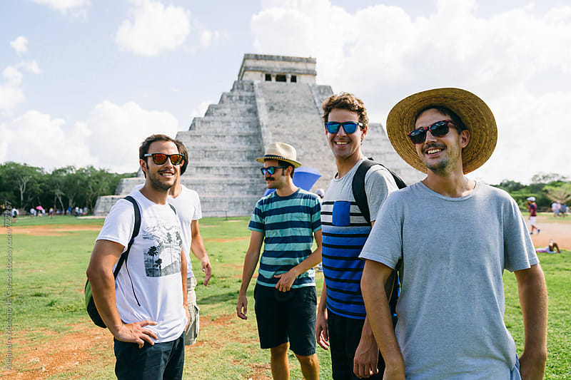 Group of men friends having fun next to Kukulkan pyramid in Chichen Itza, Mexico by Alejandro Moreno de Carlos for Stocksy United
