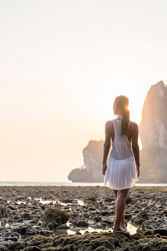 Beautiful woman in white dress watching sunset on the beach  by Soren Egeberg for Stocksy United