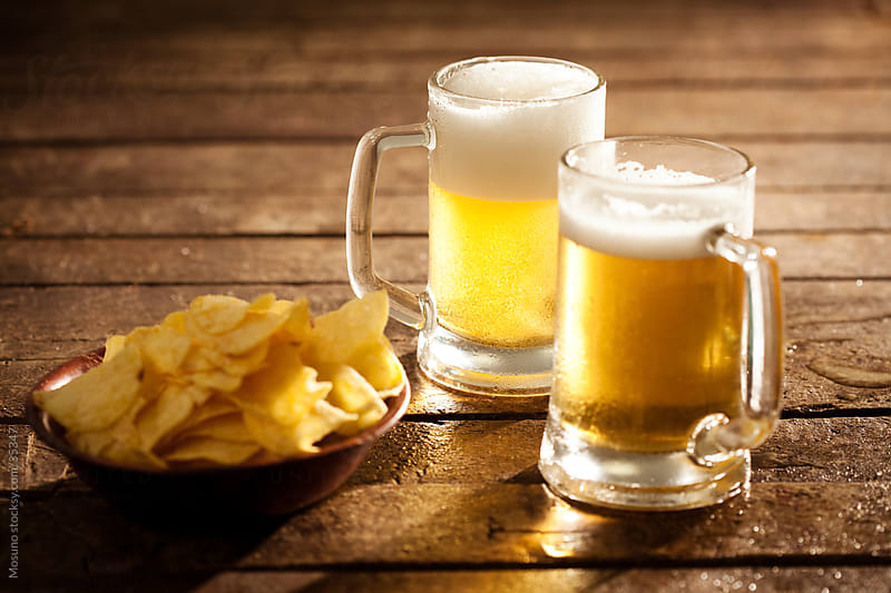Beer and chips on the bar table. by Mosuno for Stocksy United