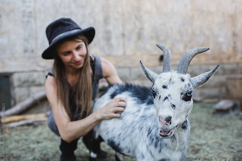 Woman and her goat in the backyard by michela ravasio for Stocksy United