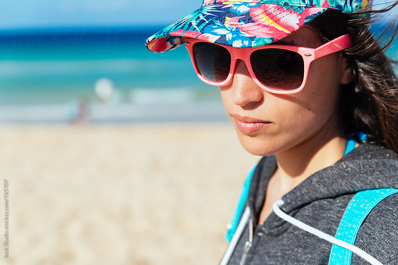 Fashion young woman wearing pink sunglasses and a colourful cap in a beach, with copyspace by Inuk Studio for Stocksy United
