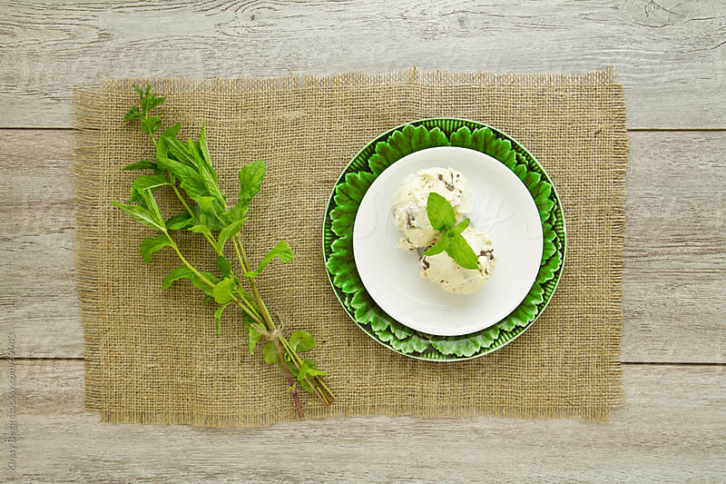 Green plate with ice cream and mint leaf stems on burlap by Kirsty Begg for Stocksy United