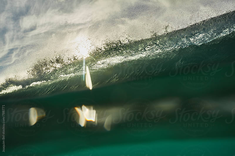 Wave's lip falling down with the sun flaring thru it. by Joaquim Bel for Stocksy United