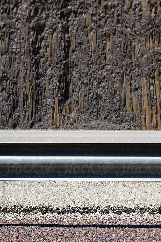 Safety railing along roadside, basalt rock wall in background, Oregon by Paul Edmondson for Stocksy United