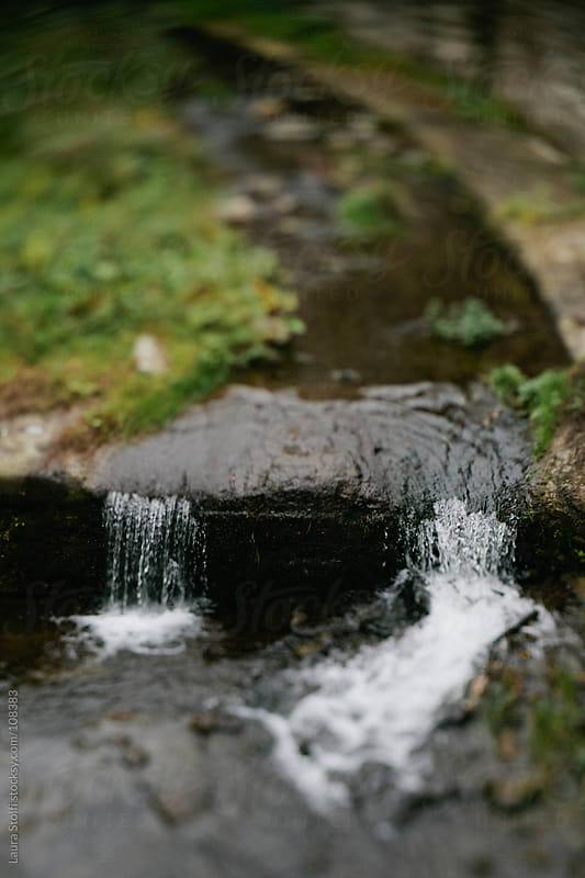 Water streaming in mountan brook in italian village by Laura Stolfi for Stocksy United