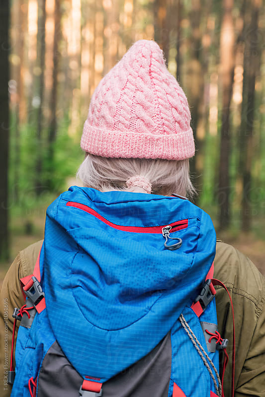 Back view of blonde backpacker in pink hat by T-REX & Flower for Stocksy United