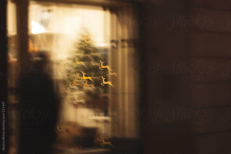 Defocused deer shape Christmas lights in a shopping window by Beatrix Boros for Stocksy United