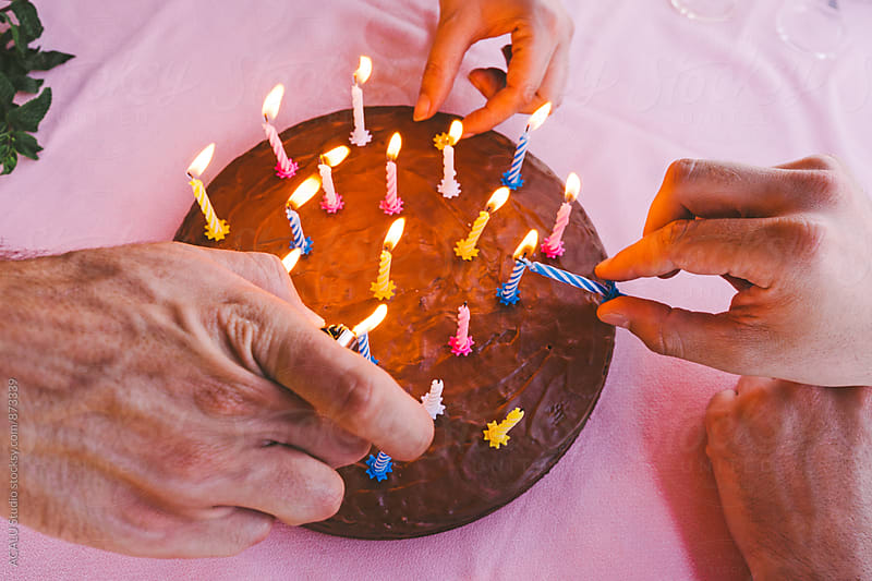 Friends lighting candles on a chocolate cake by ACALU Studio for Stocksy United