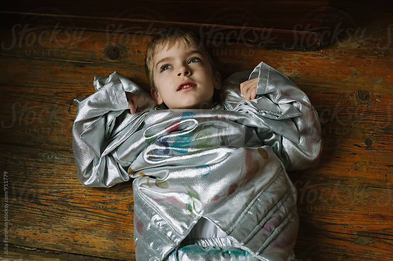 Boy in a silver costume lying on wooden floor. by Julia Forsman for Stocksy United