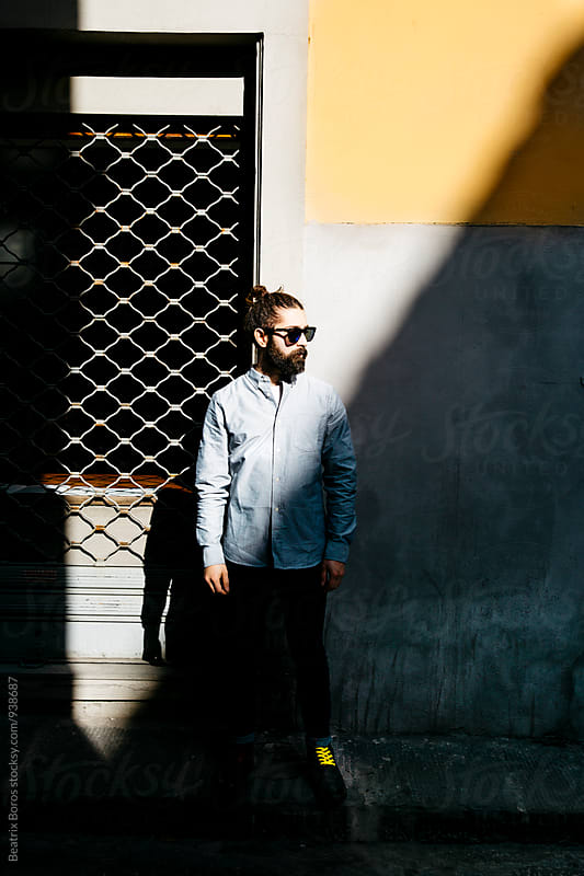 Man in sunglasses standing next to a closed shop in in half sun and half shadow by Beatrix Boros for Stocksy United