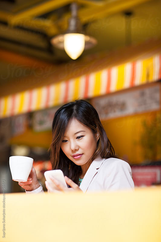 Beautiful Asian woman inside a cafe looking at her phone by Suprijono Suharjoto for Stocksy United