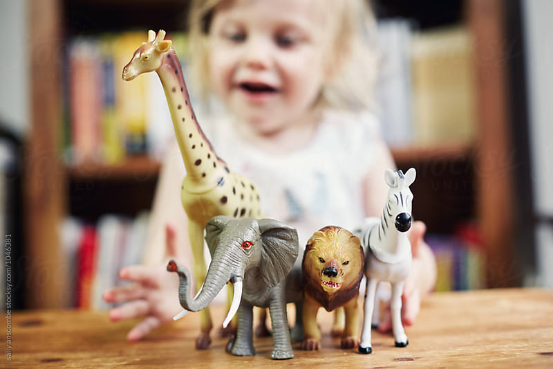 Child playing with toy animals  by sally anscombe for Stocksy United
