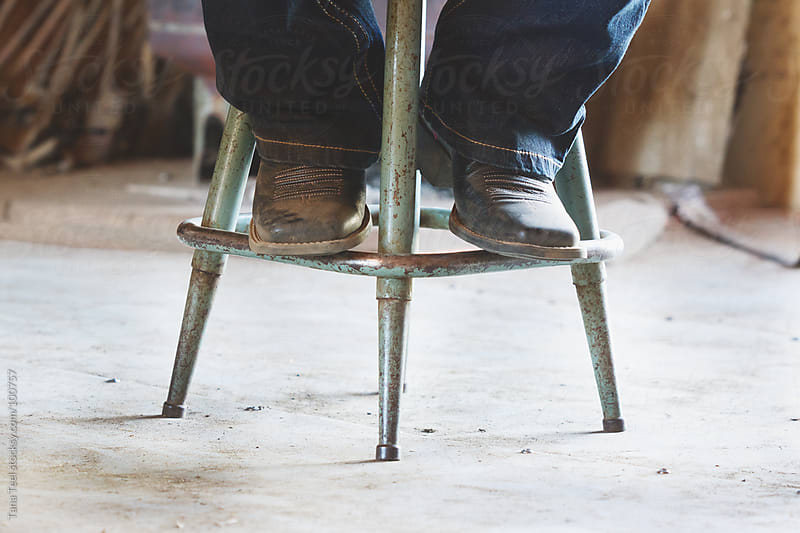 Cowboy boots on a stool by Tana Teel for Stocksy United