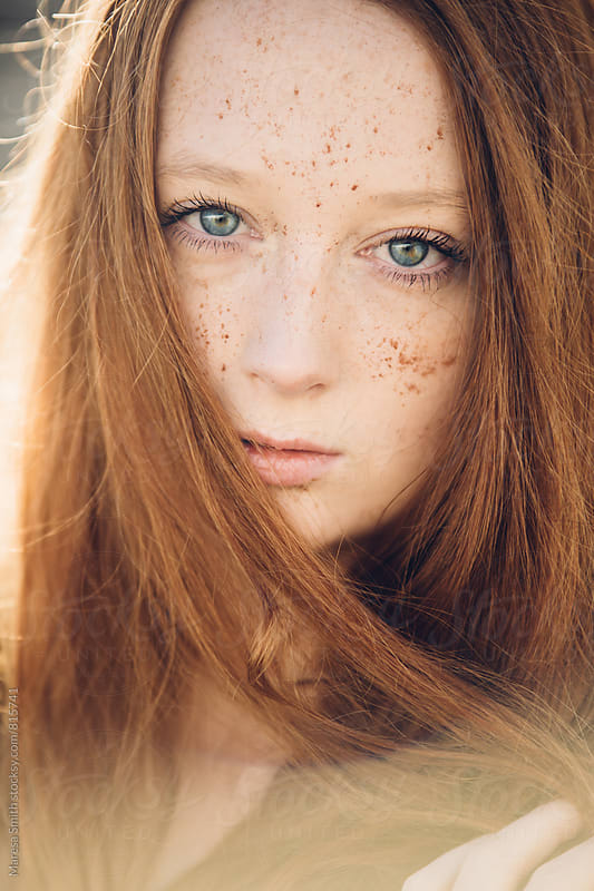 Portrait of a ginger teenager in the sunlight with freckles and long hair by Maresa Smith for Stocksy United