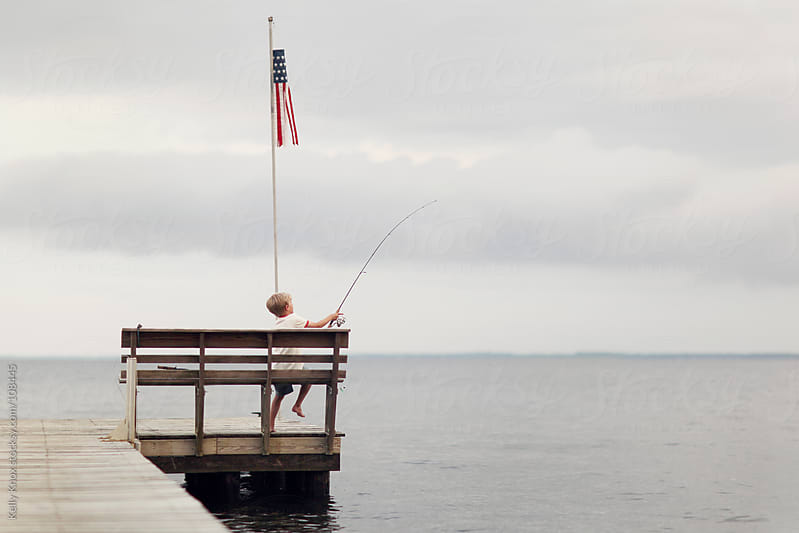 boy fishing off the end of a pier by Kelly Knox for Stocksy United