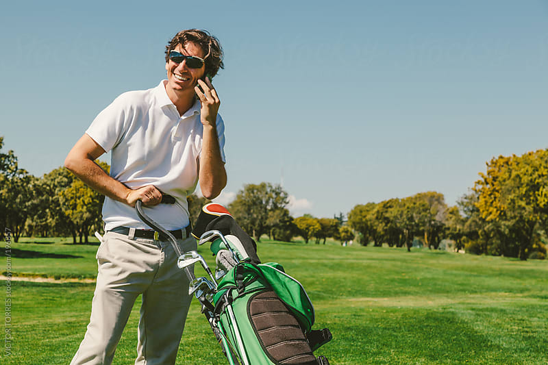 Golf Player in a Golf Course Talking by Phone by VICTOR TORRES for Stocksy United