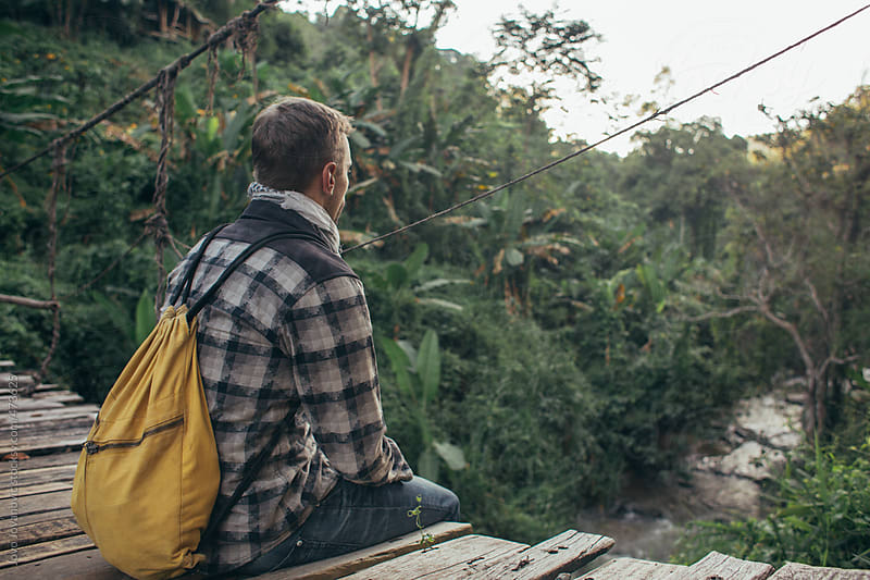 Young man with backpack sitting and thinking on a wooden bridge overlooking the jungle by Jovo Jovanovic for Stocksy United