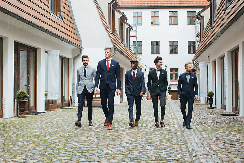 Group of Four Stylish Young Men in Suits Walking Down in Courtyard by VISUALSPECTRUM for Stocksy United
