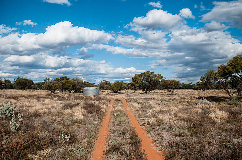 Dirt track and rain water tank in outback Australia. by Thomas Pickard for Stocksy United