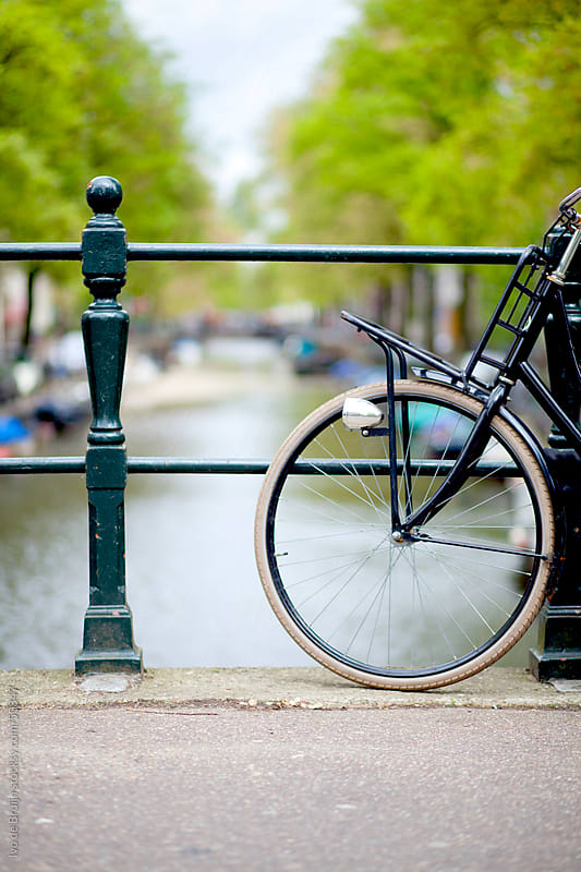 A classic bike standing on a bridge with an Amsterdam canal, trees and boats in the background by Ivo de Bruijn for Stocksy United