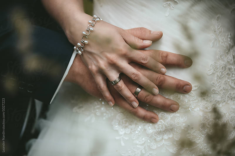 detail of caressingly bridal couple hands with wedding rings  by Leander Nardin for Stocksy United
