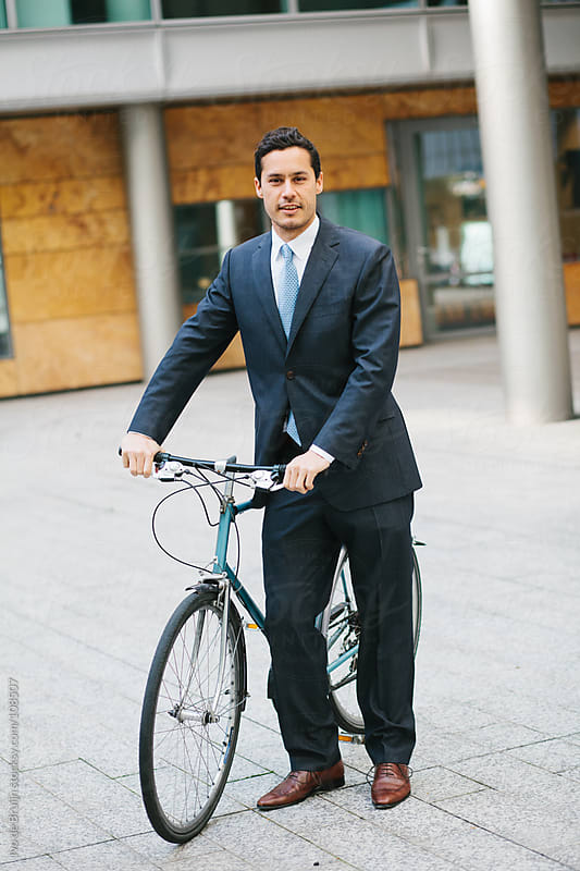 Business man in suit standing next to his bike by Ivo de Bruijn for Stocksy United