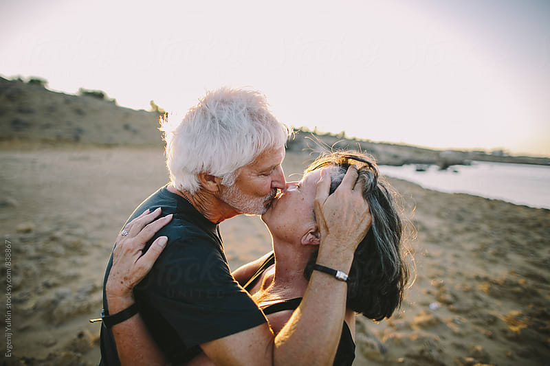 Old couple kissing by Evgenij Yulkin for Stocksy United