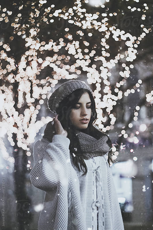 Girl posing on the street with Christmas lights behind her by Jovana Rikalo for Stocksy United