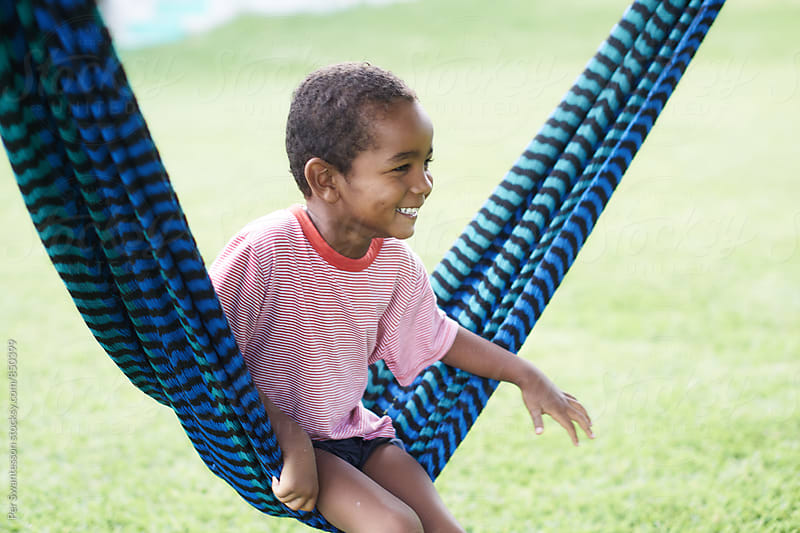 Young kid having fun in a hammock by Per Swantesson for Stocksy United