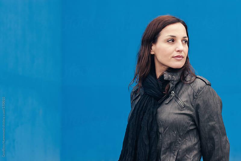 Portrait of Woman in Jacket Against Blue Wall by Geoffrey Hammond for Stocksy United