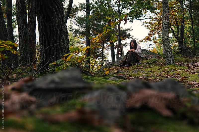 A Girl in a Forest Creates a Garland of Leaves by Deirdre Malfatto for Stocksy United