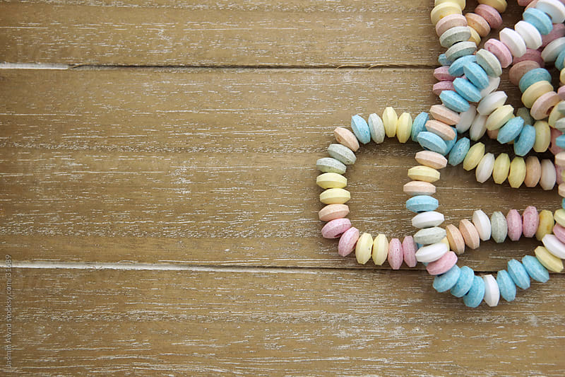 Pastel colored sweet beads necklace with wood background and copy space by Jasmin Awad for Stocksy United