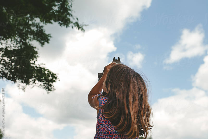 Little girl looks up at clouds through view finder by Amanda Worrall for Stocksy United