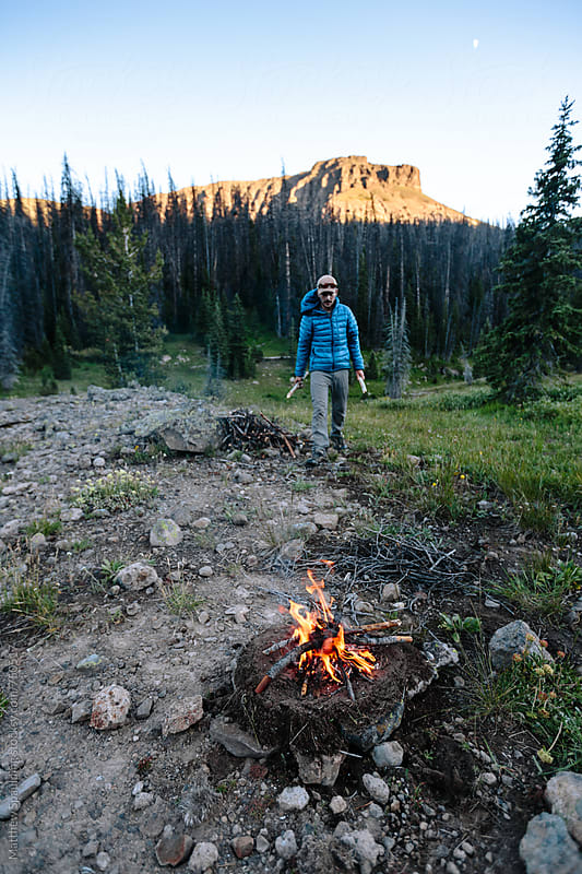 Man gathering wood and assembling small fire for camping by Matthew Spaulding for Stocksy United