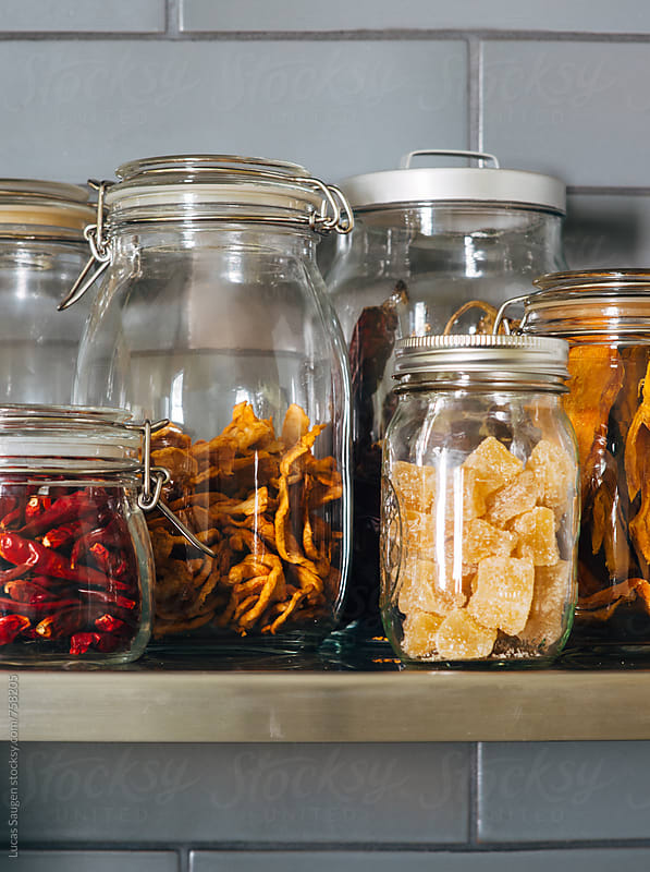 A close shot of dried or dehydrated peppers and fruits in glass jars sitting on shelf in a kitchen. by Lucas Saugen for Stocksy United