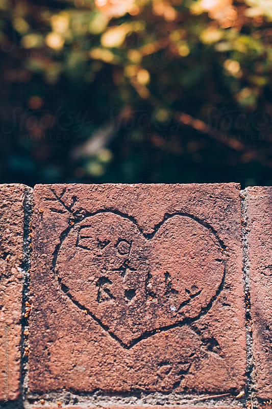 Heart engraved on a brick wall by Vera Lair for Stocksy United