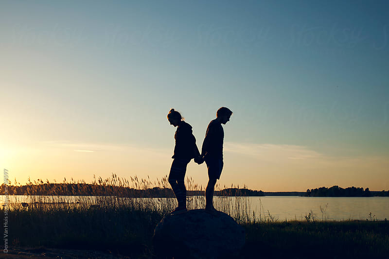 A couple enjoying the sunset around a lakeside on a warm summer night by Denni Van Huis for Stocksy United