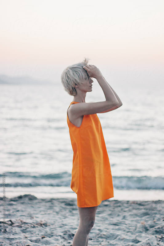 Portrait of a blonde short hair female model in orange dress on the beach at sunset from behind by Evil Pixels Photography for Stocksy United