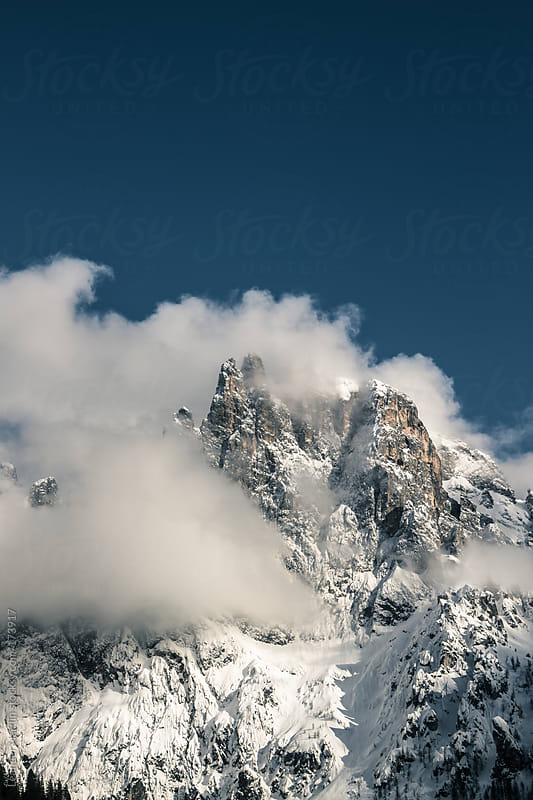 snowcovered peaks surrounded by clouds by Leander Nardin for Stocksy United
