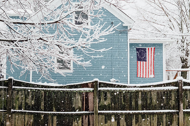 A snowy wooden fence with a blue house and american flag in background. by J Danielle Wehunt for Stocksy United