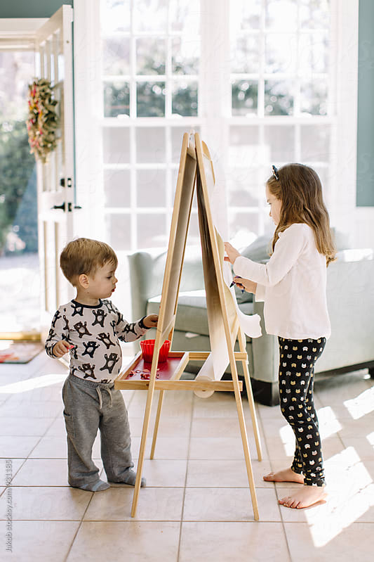 Cute young girl and boy painting using an easel stand by Jakob for Stocksy United