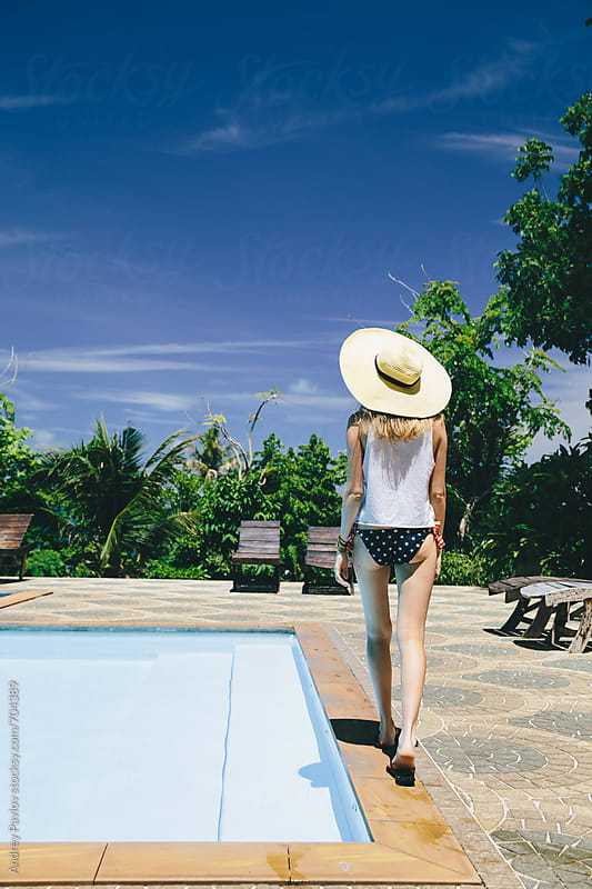 Woman walking near pool by Andrey Pavlov for Stocksy United