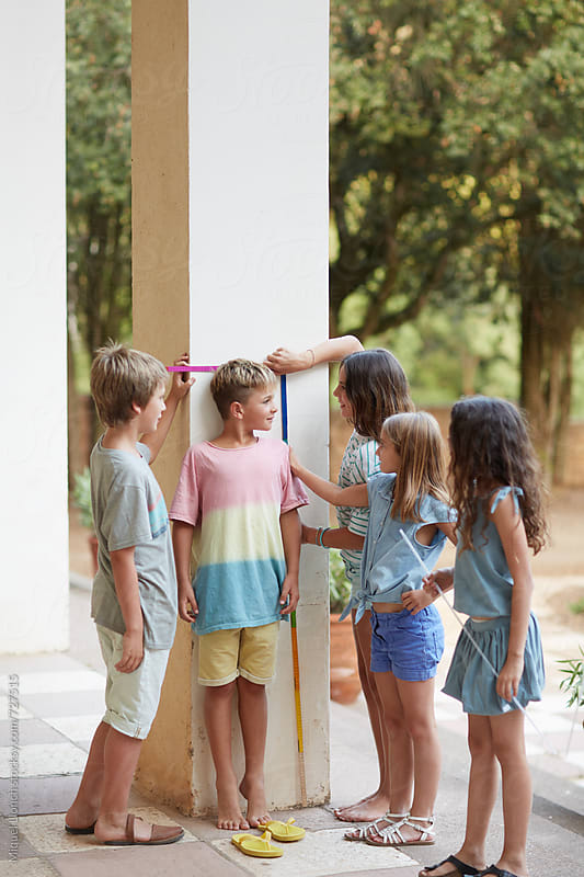 Kids measuring their height in a party by Miquel Llonch for Stocksy United