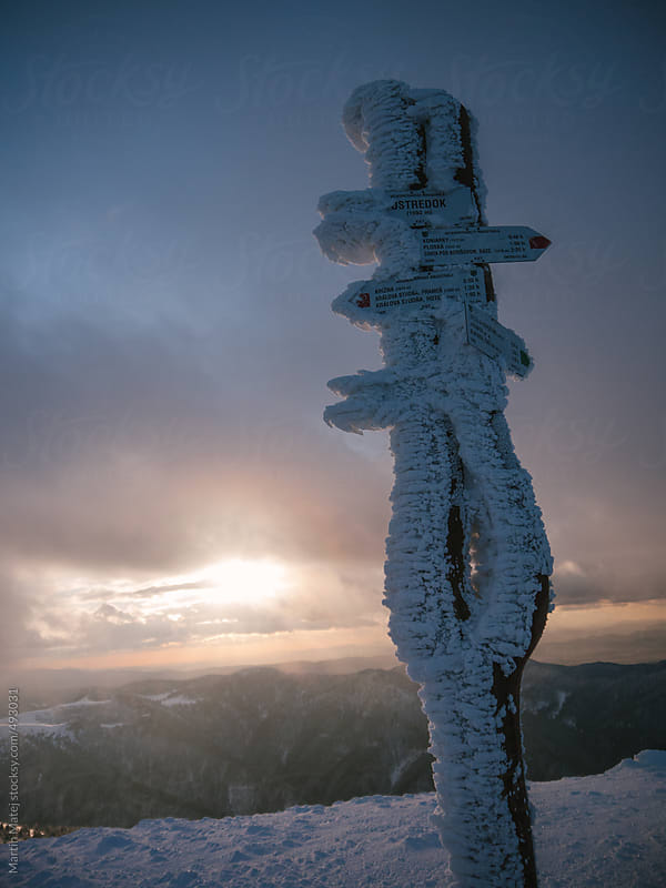 Signpost covered with snow in the mountains by Martin Matej for Stocksy United