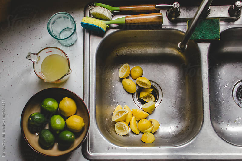 Bowl of citrus fruit  and cup of lemon juice beside sink of squeezed lemons by Lindsay Crandall for Stocksy United