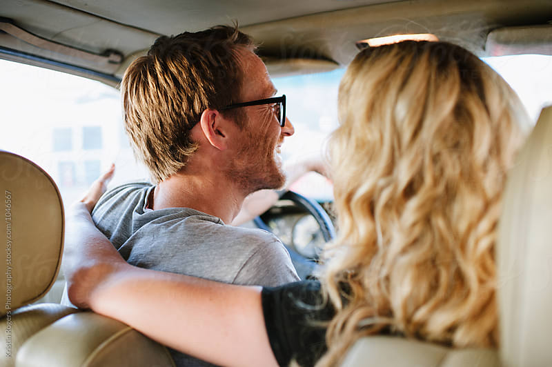 Couple smiling dricing in car by Kristin Rogers Photography for Stocksy United