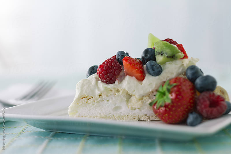 Pavlova slice with summer berries horizontal by Kirsty Begg for Stocksy United