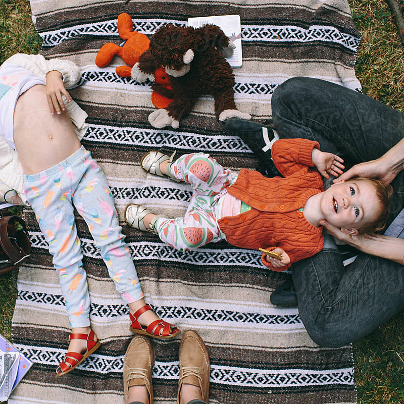 Family on a blanket by Ali Lanenga for Stocksy United