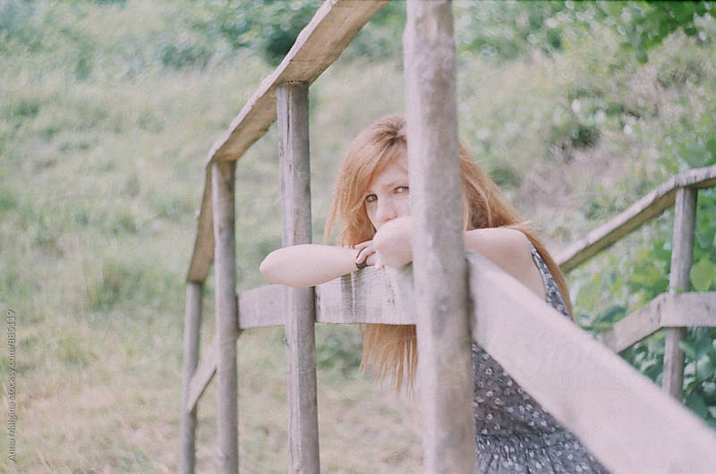A film portrait of a young redhead woman sitting on the wood bridge by Anna Malgina for Stocksy United