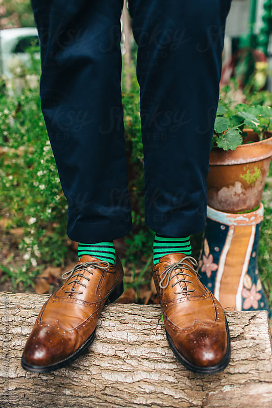 A mans brown oxford shoes & green socks  by Kristen Curette Hines for Stocksy United